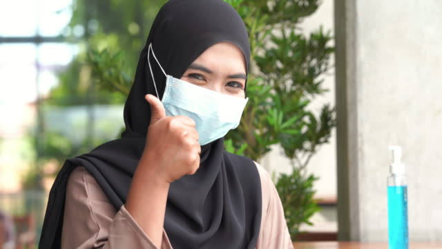 young asian muslim woman using antibacterial hand sanitizer , thumbs up for good condition - good condition stock videos & royalty-free footage