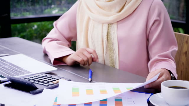 Young Asian Muslim woman wearing hijab working with  analyzing market data documents and counting on calculator at office
