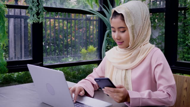 Young Asian Muslim woman wearing hijab working with laptop computer and mobile phone at office