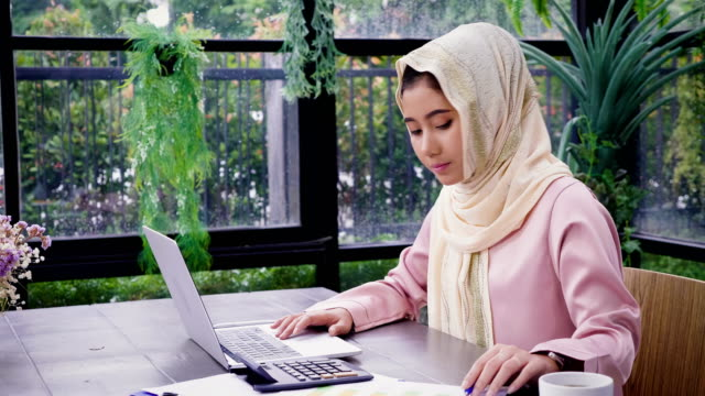 Young Asian Muslim woman wearing hijab working with laptop computer and documents at office