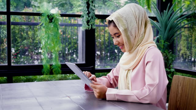 Young Asian Muslim woman wearing hijab working with tablet computer at home office