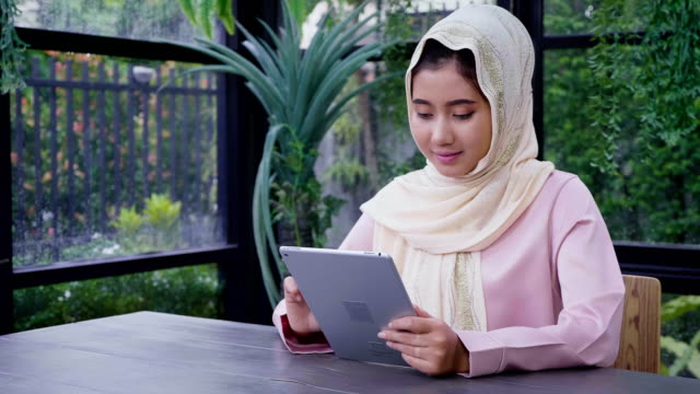Young Asian Muslim woman wearing hijab working with tablet computer and and looking in the camera