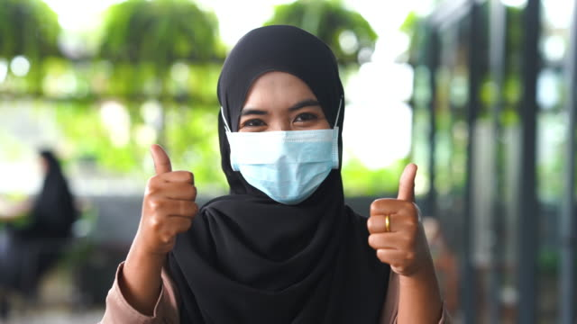 young asian muslim woman with surgical mask protection with good gesturing , thumbs up - traditional clothing stock videos & royalty-free footage