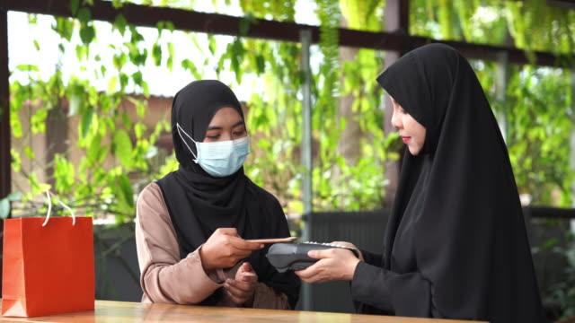 junge asiatische muslimische frauen online-shopping, contect zahlung mit mobiler app-technologie, ramadan zu hause - onlinebanking stock-videos und b-roll-filmmaterial
