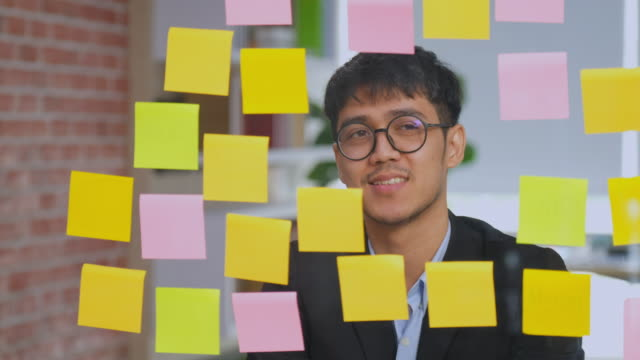 young asian office man reading adhesive note paper on glass window at office, people at office lifestyle - sticky stock videos and b-roll footage