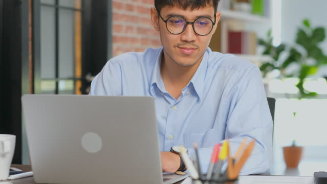 young asian office man working with laptop computer and reading paperwork at office desk, people and technology, office lifestyle concept - programmer stock videos & royalty-free footage