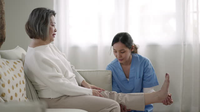 young asian physiotherapist doing exercises with his senior patient - mature women stock videos & royalty-free footage