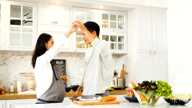 young asian pregnant woman with husband dancing in kitchen at home - kitchen worktop stock videos & royalty-free footage