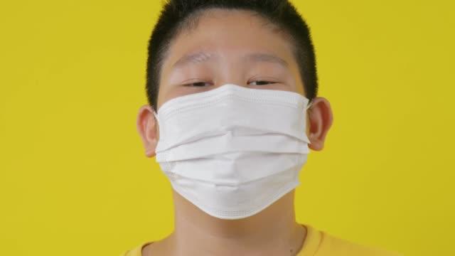 vidéos et rushes de jeune garçon asiatique de préadolescent utilisant le masque au-dessus du fond jaune. - poumon humain