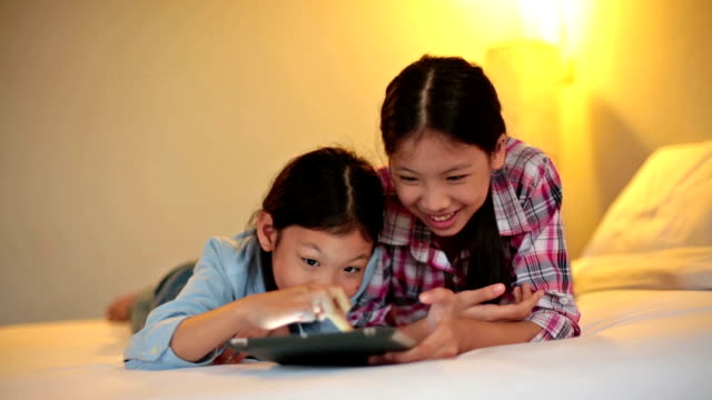 Young Asian Siblings with Wireless Tablet