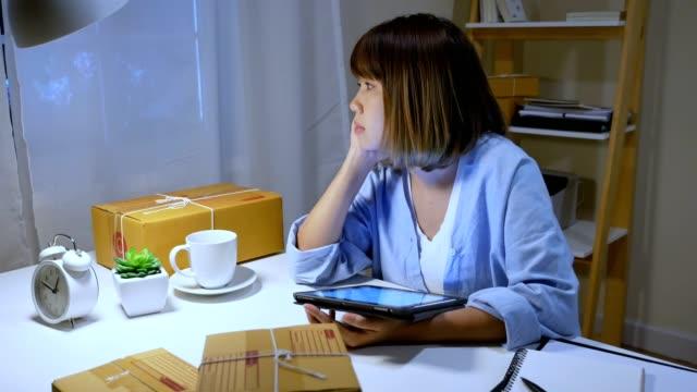 アジアの若い中小企業経営者は、自宅で夜遅くまで働いて気分が悪くて疲れを感じています。 - exhaustion点の映像素材/bロール
