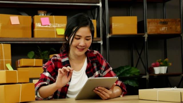 vídeos de stock, filmes e b-roll de jovem asiático pequeno empresário usando tablet digital e trabalhar em casa. marketing online entrega embalagem ou conceito de mulher freelance. - e commerce