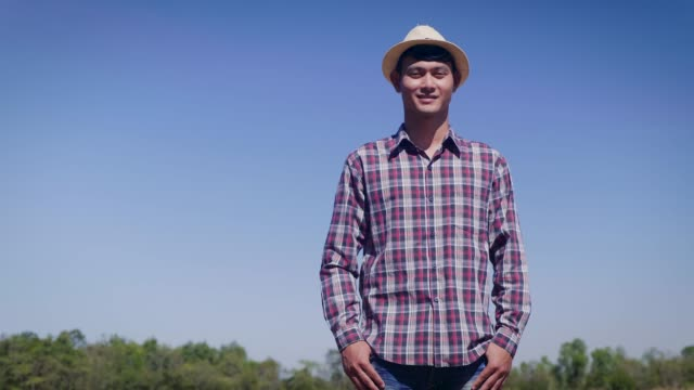 young asian smiling man or farmer looking at camera in cultivated field - cibo biologico video stock e b–roll