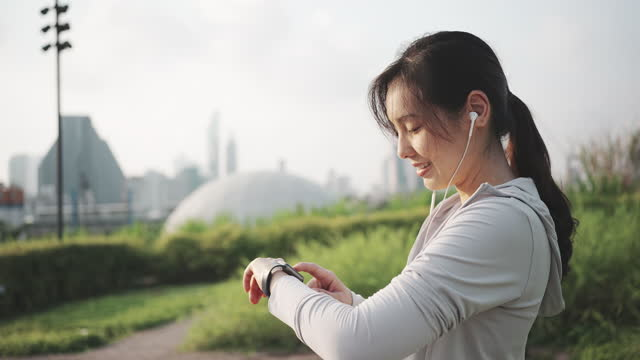 young asian sporty woman using smart watch for monitoring her running performance in morning - interval start stock videos & royalty-free footage