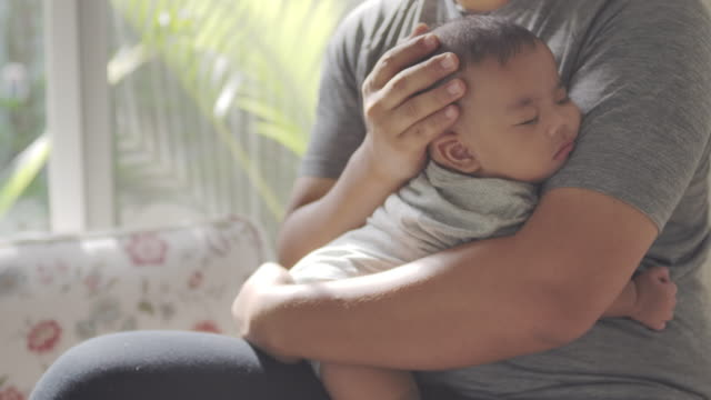 a young asian stay-at-home father is holding and calming the baby to sleep at the living room day time with love and care. - genderblend stock videos & royalty-free footage