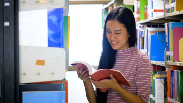 young asian student girl reading a book in college library, education and school concept - bookshelf stock videos & royalty-free footage