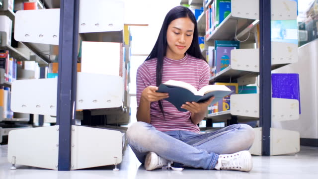 Young Asian student girl reading a book in college library, education and school concept