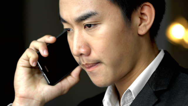 young asian thai businessman on the mobile phone working in cafe - mack2happy stock videos and b-roll footage