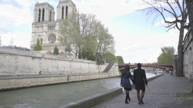 Young Asian tourist couple walking along the River Seine Paris