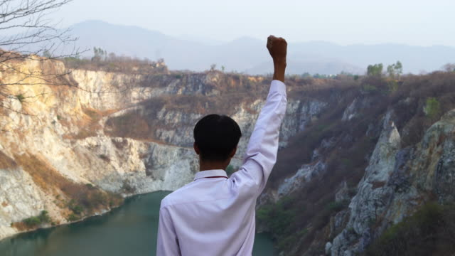 young asian tourist man feel freedom and pose raise one's hand for cheering and success sign at stone canyon in chonburi province , thailand - chonburi province stock videos & royalty-free footage