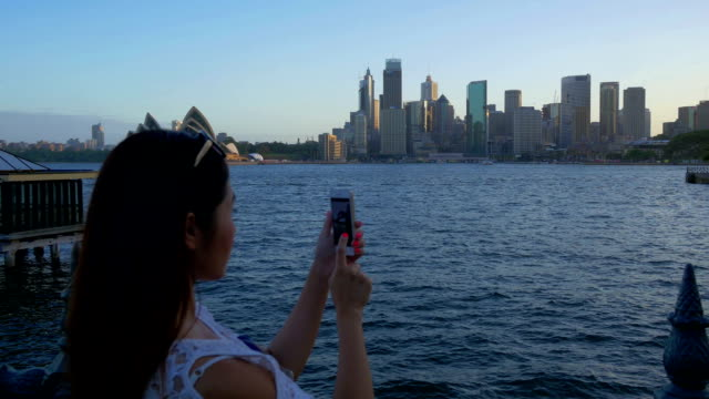 Young Asian tourist taking pictures of Sydney