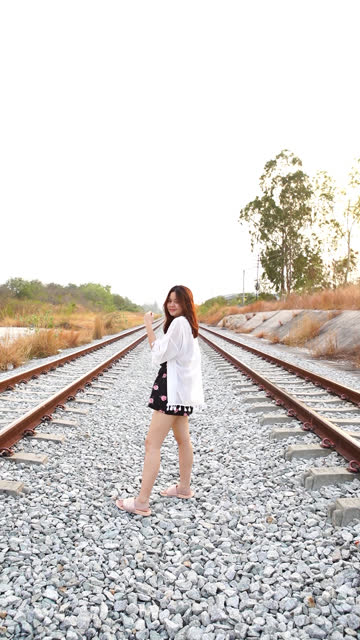 young asian tourist woman walking alone on railroad tracks , extreme terrain scene , vertical format video for smart phone - missing people stock videos & royalty-free footage