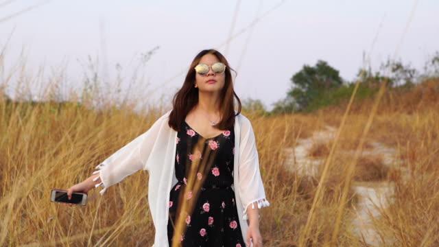 stockvideo's en b-roll-footage met jonge aziatische toerist wowman rusten voelen vrijheid en armen uitgestrekt op gedroogde plantenveld , extreme terrein scène - alleen één tienermeisje