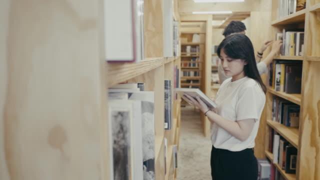 アジアの若い大学生が図書館で本を探す(スローモーション) - 見つける点の映像素材/bロール