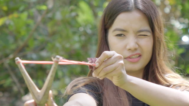 Young Asian woman aiming with a slingshot