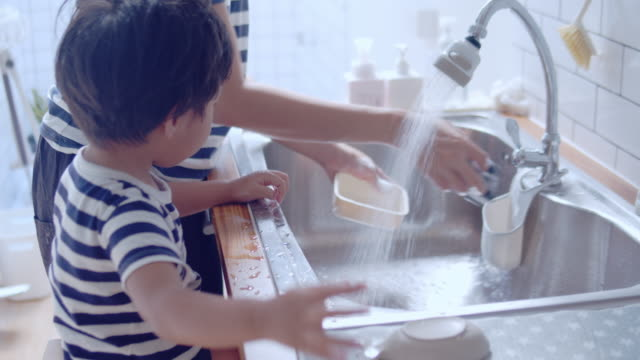 young asian woman and baby boy washing dishes in kitchen. - lavori di casa video stock e b–roll