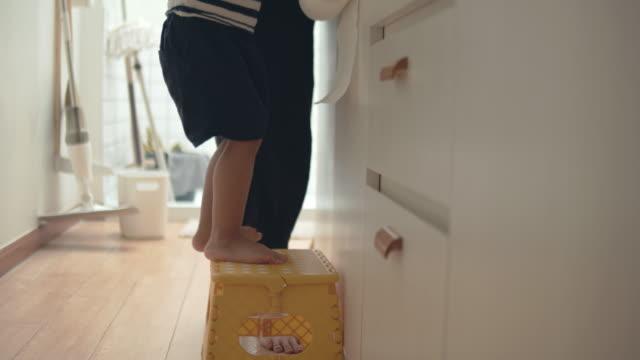 stockvideo's en b-roll-footage met jonge aziatische vrouw en baby jongen wassen gerechten in de keuken. - gootsteen