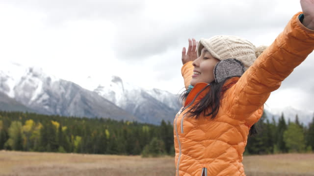 young asian woman arms outstretched in snow capped mountain - arms outstretched stock videos & royalty-free footage