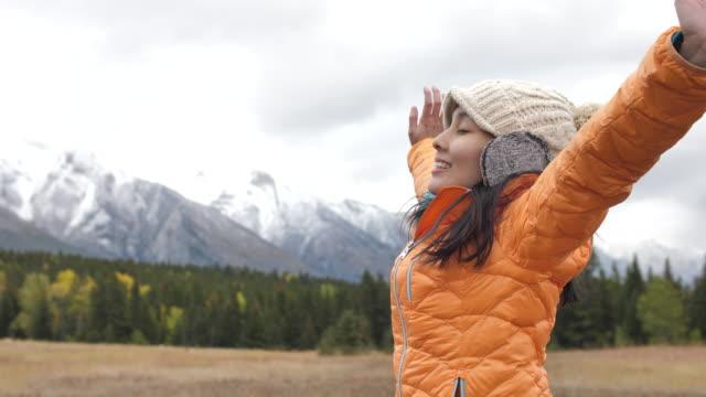 雪の中で若いアジア女性の両腕を頂いた山 - 腕を広げる点の映像素材/bロール