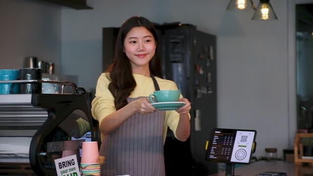 vídeos y material grabado en eventos de stock de joven asiática, barista, dueño de café, camarera sirviendo una taza de café al cliente en el mostrador en la cafetería de la cafetería, cámara lenta - dar