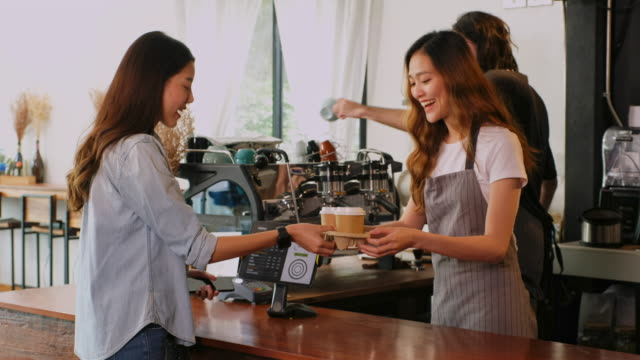 young asian woman barista, cafe owner, waitress serving take out coffee to customer at counter in coffee shop cafe - coffee shop stock videos & royalty-free footage