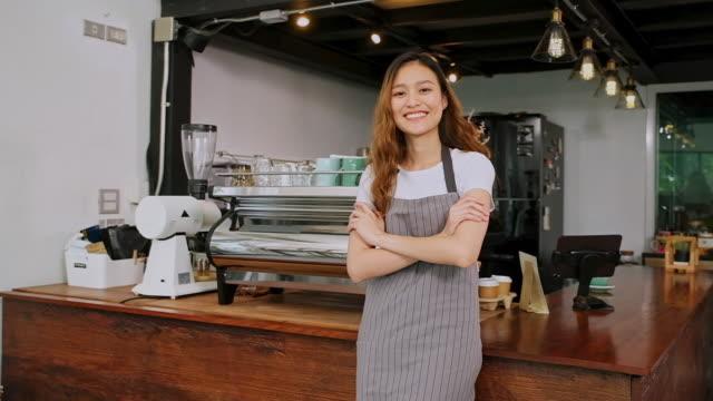 コーヒーショップカフェのカウンターに立ちながらカメラを見ながら笑顔を浮かべたアジアの若い女性バリスタ、スローモーション - ウェイトレス点の映像素材/bロール