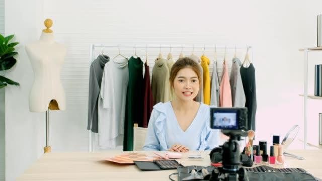 vidéos et rushes de jeune femme asiatique beauté blogger affichage cosmétique lors de l'enregistrement comment faire tutoriel vidéo par caméra, notion de vlog, beauté et mode communication de personnes et de la technologie - influenceur