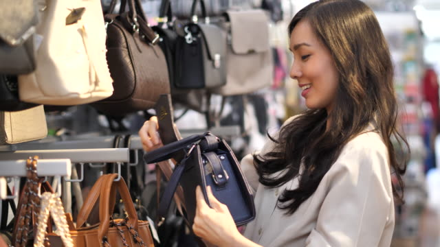young asian woman browsing in the purse fashion store. - quality stock videos & royalty-free footage