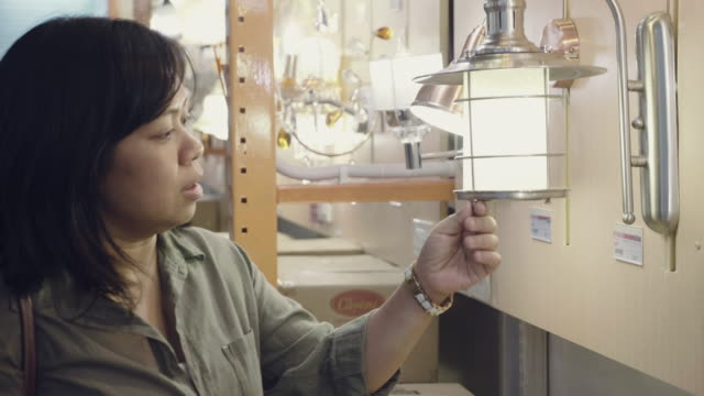 Young asian woman buying lamps at department store.