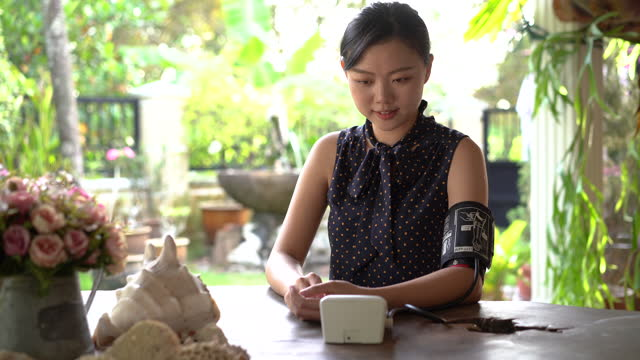 young asian woman checking blood pressure at home - blood pressure gauge stock videos & royalty-free footage