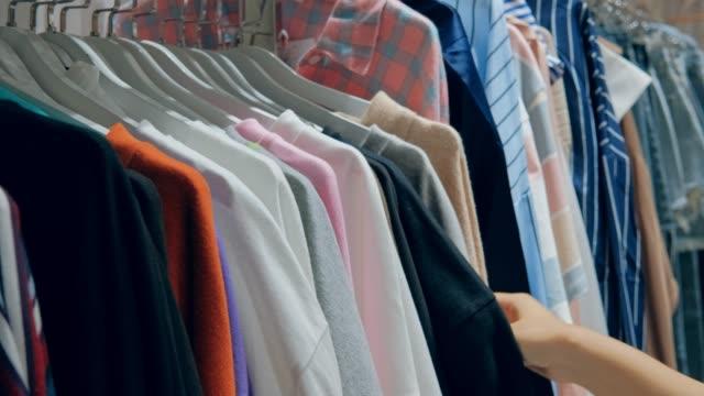 ung asiatisk kvinna väljer kläder i the store shopping mall - skjorta bildbanksvideor och videomaterial från bakom kulisserna