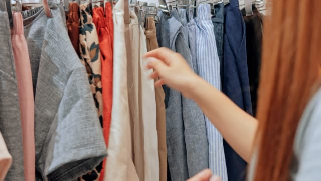 young asian woman chooses clothes in the store shopping mall - clothing store stock videos & royalty-free footage