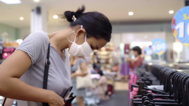 young asian woman choosing and buying clothes, bag and accessories apparel in shopping mall with face mask protection. - textile stock videos & royalty-free footage