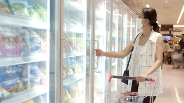 young asian woman choosing and picking product from deep freezer in supermarket store with  face mask protection from dust and virus for healthy. - cibi surgelati video stock e b–roll