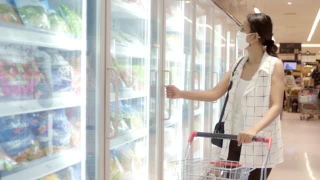 giovane donna asiatica che sceglie e raccoglie il prodotto da deep freezer nel negozio del supermercato con protezione della maschera facciale da polvere e virus per la salute. - cibi surgelati video stock e b–roll