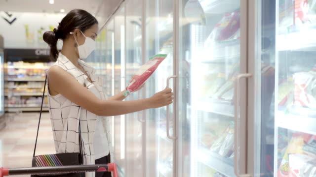 vídeos de stock, filmes e b-roll de jovem mulher asiática escolhendo e colhendo produto do freezer profundo na loja de supermercado com proteção contra máscara facial contra poeira e vírus para saudável. - shopping center