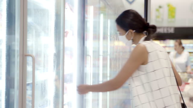 young asian woman choosing and picking product from deep freezer in supermarket store with  face mask protection from dust and virus for healthy. - frozen food stock videos & royalty-free footage