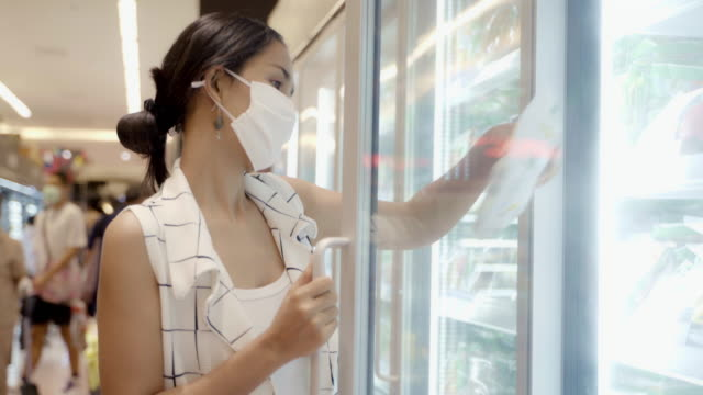 vídeos y material grabado en eventos de stock de mujer joven asiática eligiendo y recogiendo producto de deep freezer en la tienda de supermercados con protección de máscara sin rostro contra el polvo y virus para saludable. - pasillo objeto fabricado