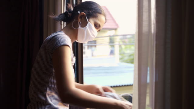 young asian woman cleaning windows in the evening with sunset backlight background and face mask protection. do the chore concept. - detersivo per bucato video stock e b–roll