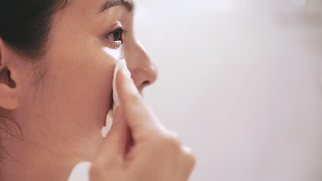 stockvideo's en b-roll-footage met de jonge aziatische vrouw reinigt haar gezicht - poreus